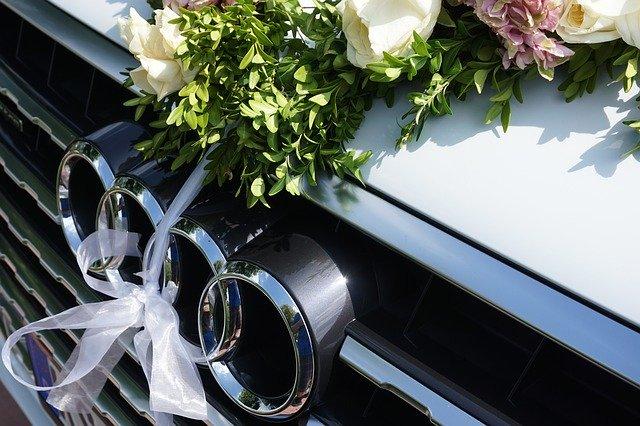 automobil audi znak na tmavém autě, nahoře je ozdoba z květin, bílá mašlička jako na svatbu